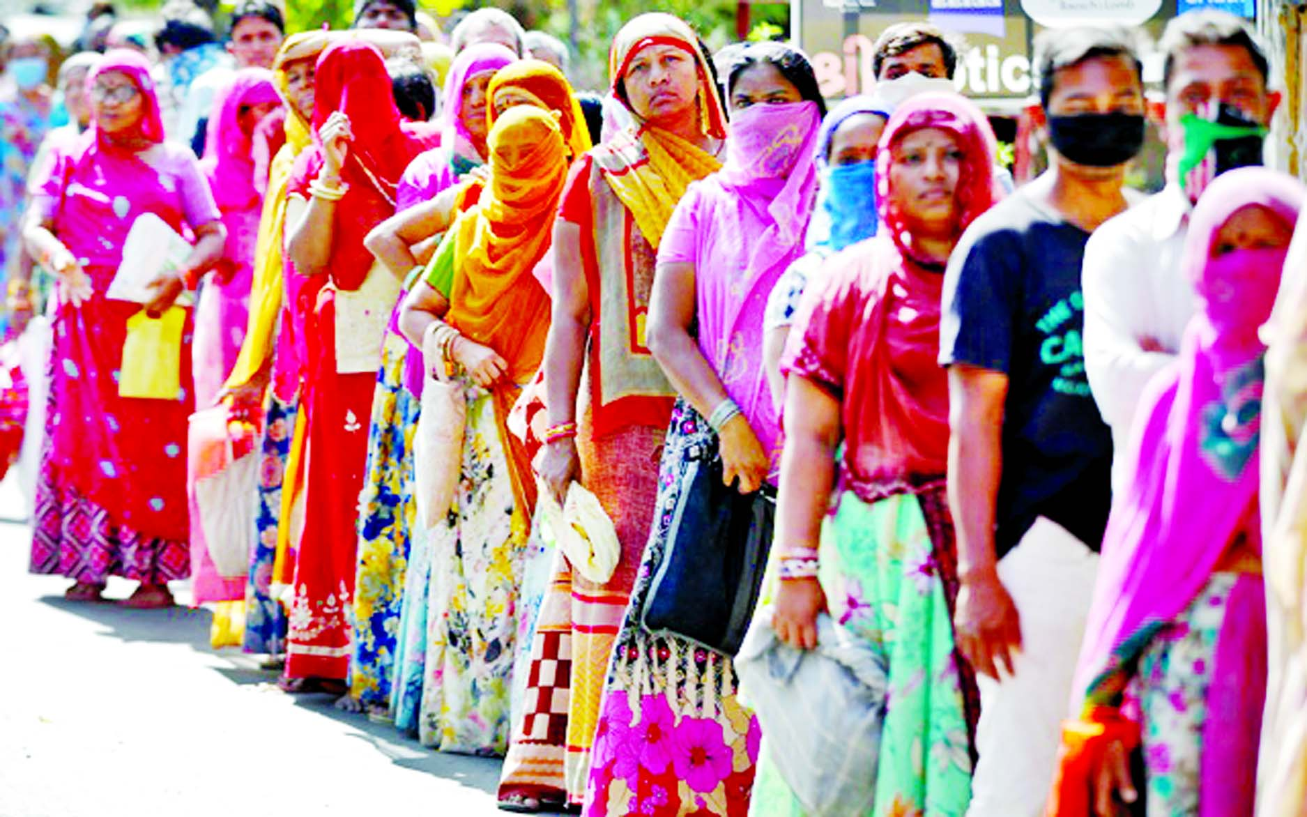 People stand in a queue as they wait for their turn to receive free food grains from a government controlled grains store during a 21-day nationwide lockdown to slow the spreading of coronavirus disease in Ahmedabad, India on Wednesday.