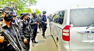 RAB personnel stop a microbus and query the passengers at Shanir Akhra in Dhaka on Thursday as the government orders citizens to stay at home to enforce home quarantine and social distancing during countrywide shutdown amid spread of coronavirus.