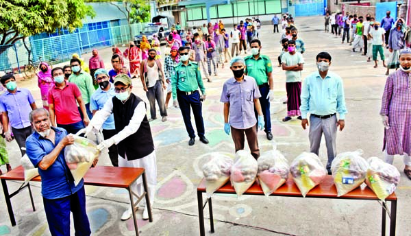 Chairman of the Governing Body of the city's Willes Little Flower School and College  Arifur Rahman Titu distributing foods among the destitute on the premises of the institution on Saturday. Foods were bought from the joint aid of the teachers and governing body of the institution.