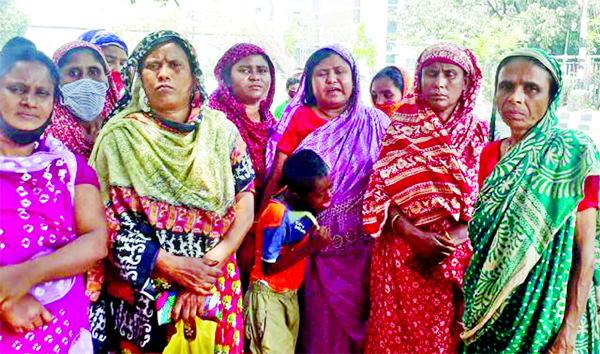 Distressed women are waiting for the relief goods defying the order of social distance in city's Green Road area on Sunday.