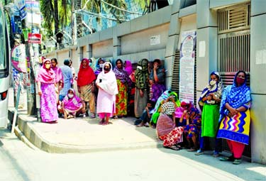 Destitute women wait for relief in front of a house at Malibagh in the city on Monday as they lost income due to the nationwide shutdown enforced to contain spread of coronavirus.