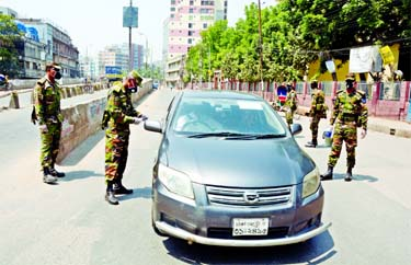 Army personnel intercept a private car on the face of Babu Bazar Bridge on Tuesday to prevent people enter or leave in Dhaka to contain spread of COVID-19.