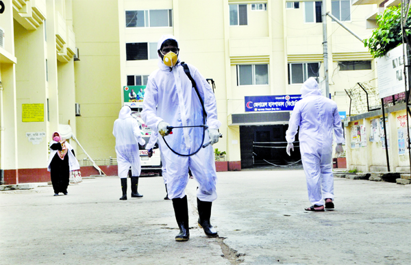 Employees of Narayanganj Victoria General Hospital spraying germicide around the hospital on Wednesday as the entire Narayangonj district was put under the total lockdown over coronavirus fear.