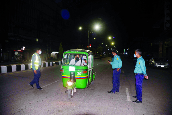 Police intercept a CNG Auto at a checkpoint in front of Modhumita Cinema Hall in Dhaka on Friday evening during lockdown in response to the outbreak of the coronavirus pandemic in the city.
