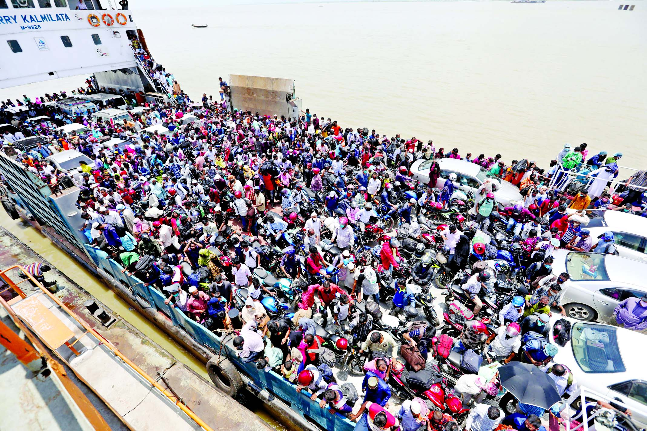 Thousands of people crowd at a ferry for crossing River Padma through Kathalbari- Shimulia route in their desperate bid to return Dhaka after celebrating Eid-ul-Fitr defying the social distancing and the risk of coronavirus infection. This photo was taken from Mawa Ferry Terminal on Friday morning.