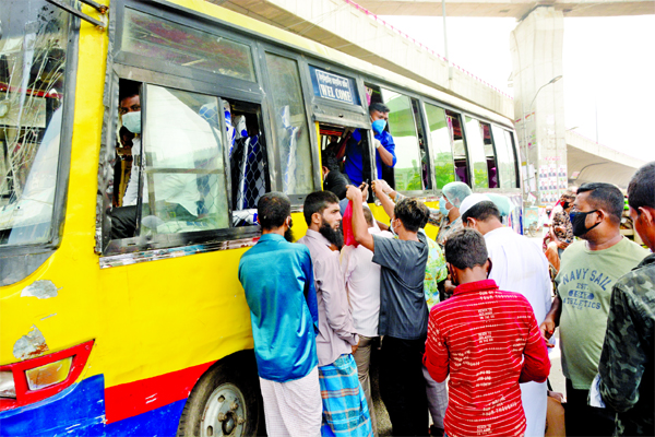 Passengers try to get in a bus at the capital's Jatrabari area on Sunday as some public buses return to the city roads a day before reopening of public transport after the nationwide shutdown.