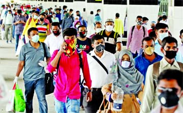 Passengers walk past on a platform at Kamalapur Railway Station on their way back Dhaka on Sunday as Bangladesh Railway resumes intercity train services after 66-days of nationwide coronavirus shutdown.