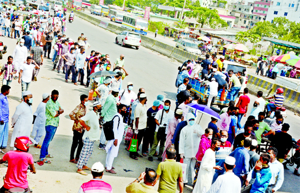Commuters wait for public bus at the capital's Rayer Bazar on Monday, a day after the authorities reopened offices and transport services in a restricted manner.