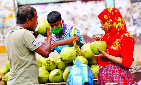 Exhausted by the scorching summer heat, thirsty pedestrians take green coconut water at Paltan area in the capital on Friday.