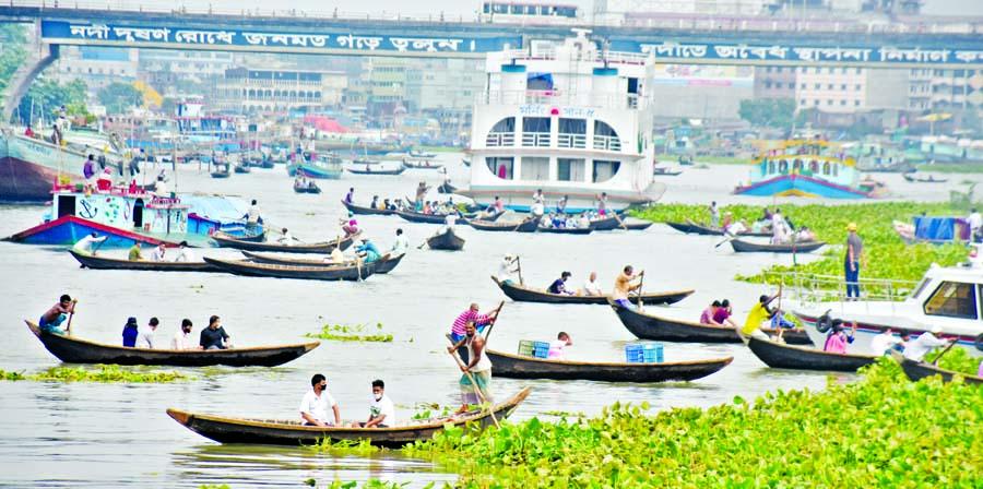Hundreds of commuters continue to cross the Buriganga River boarding small wooden boats taking risk of lives although 33 people died very recently when a small launch sank in the river after a larger one crashed into it near Sadarghat Terminal in the capital. This photo taken on Monday from underneath Babubazar the Bridge shows that boats ply on the river negotiating cargo vessels and passenger launches with huge accident risk.