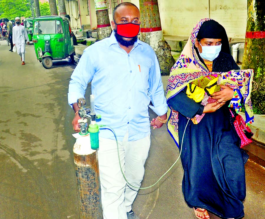 Anxious parents take a new-born to Chattogram Medical; College Hospital along with an oxygen cylinder when the baby's condition deteriorates a few hours after birth at a private clinic.
