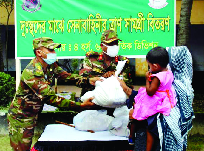 A team of the Bangladesh Army in Rangpur distributes reliefs among the poor people on Wednesday.