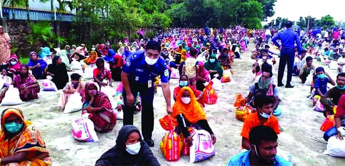 Asp Rakibul Hasan Russele on behalf of ex-ICP distributes relief among the flood victims at Dewanganj upazila of Jamalpur district on Tuesday.