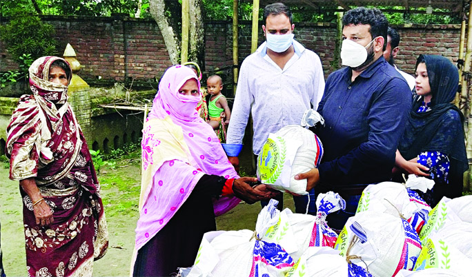 Shahadat Hossain Munna, Vice-Chairman of Srishti Human Rights Society distributes reliefs among the flood affected people at Sanyasir Char Union of Shibchar upazila, Madaripur on Wednesday.