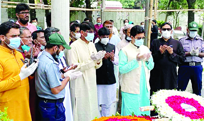DSCC Mayor Sheikh Fazle Noor Taposh, among others, offers Munajat after placing wreaths at the grave of Bangamata in the city's Banani Graveyard on Saturday marking her 90th birth anniversary.