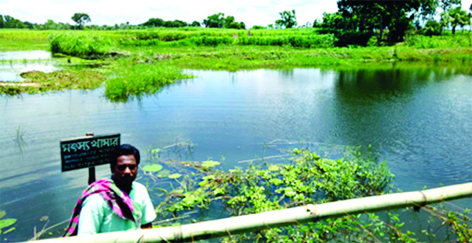A farmer with gloomy face is seen beside his pond that washed away by rainwater which cost him Tk4 lakh loss of fish business. This photo was taken from Char Laxmipur village at Modhukhali upazila of Faridpur.