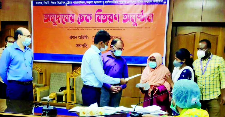 Deputy Commissioner of Dhaka Shahidul Islam distributes cheques of financial assistance among the patients afflicted with cancer, paralysis and kidney disease at the seminar room of his office on Wednesday.