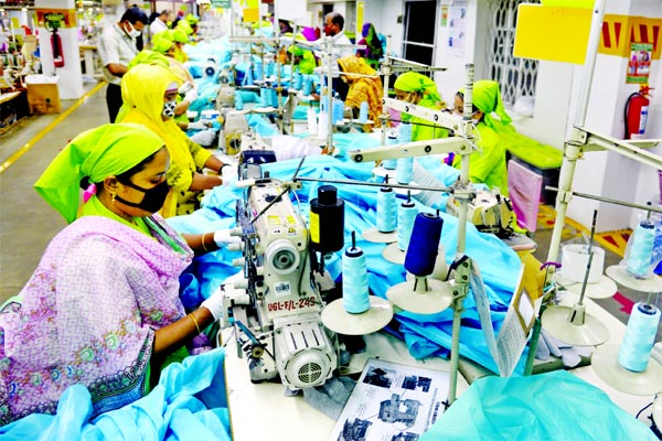 Workers are seen producing disposable medical gowns at a factory in Dhaka.