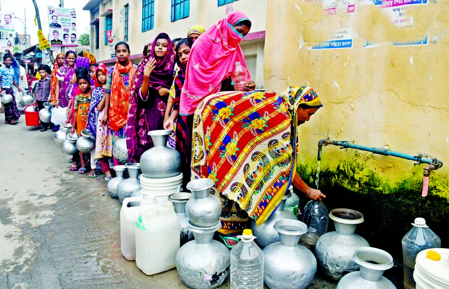 Women and girls stand in queue at a water-tap of Dhaka WASA with jerrycans, pitchers, and bottles at Dania, Jatrabari in the capital. They alleged of dirty and stinky supply water which force them to collect water from the tap every day. The photo was taken on Saturday.