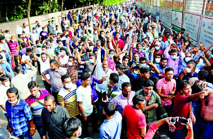 Bangladeshi expatriate workers, who get stranded at home during Covid-19 pandemic, block road in front of Saudi Airlines office at Sonargaon Hotel in the capital on Monday seeking air tickets to join their workplaces again.