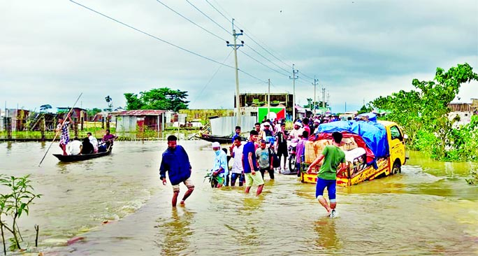 People wade through a submerged road with flood waters all around Biswambarpur upazila in Sunamganj on Friday as the Surma River was flowing 60 centimeters above danger level amid excessive rainfall in Meghalaya and Assam of India triggering flash flood in the low-lying areas of Sylhet and Sunamganj districts.