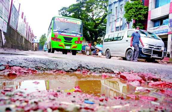 Vehicles struggle to ply on Topkhana road in the capital as a big pothole developed there due to construction work of Metro Rail.  This photo was taken on Friday.