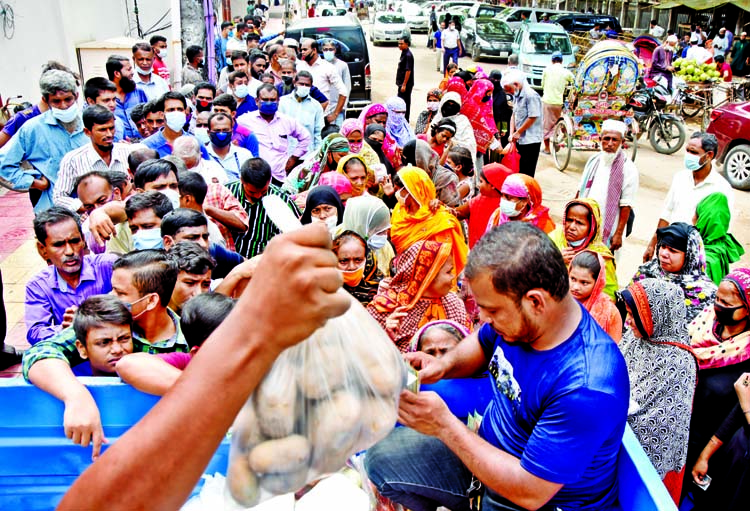 People queue up in front of a Trading Corporation of Bangladesh (TCB) truck near the National Press Club in the capital to buy potatoes at subsidized price on Wednesday. TCB started the open market sale (OMS) of potatoes at Tk 25 per kilogram from yesterday in face of sharp rise in prices of the key vegetable.