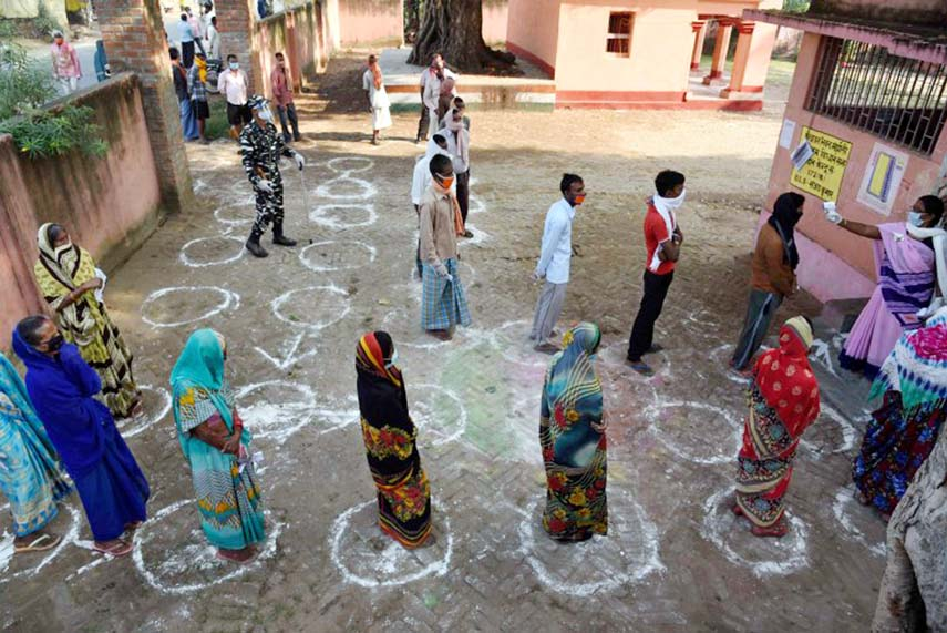 Voters queue up, maintaining distancing, at a polling station at Paliganj, Bihar.