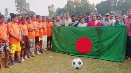 The participants of the exhibition football match with national flag and the guests pose for a photo session at Chakmirpur High School ground in Daulatpur upazila, Manikganj district on Friday.