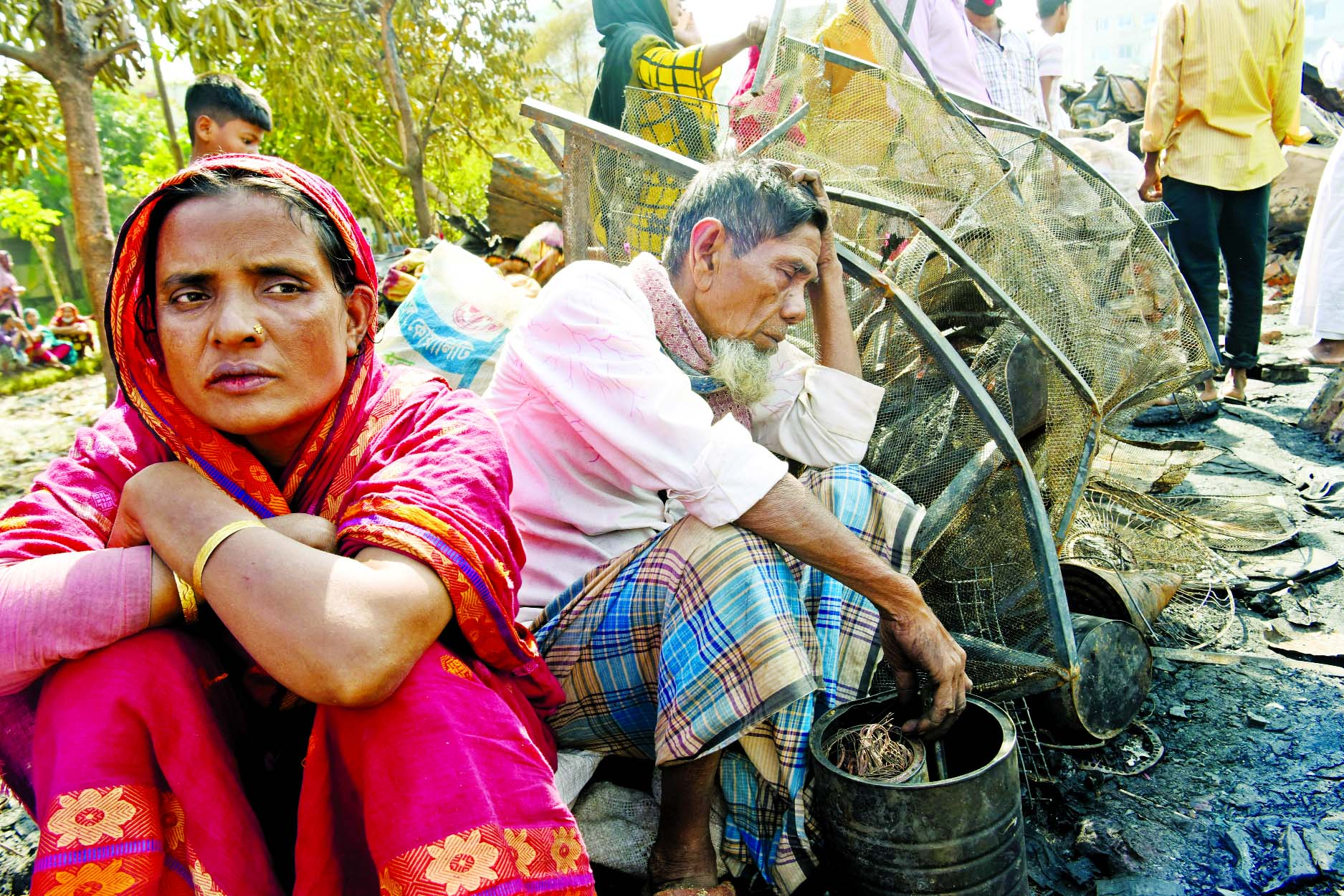People are seen sitting in distressed condition as their shanties gutted in fire. This photo was taken from Sattala Basti, Mohakhali in the capital on Tuesday.