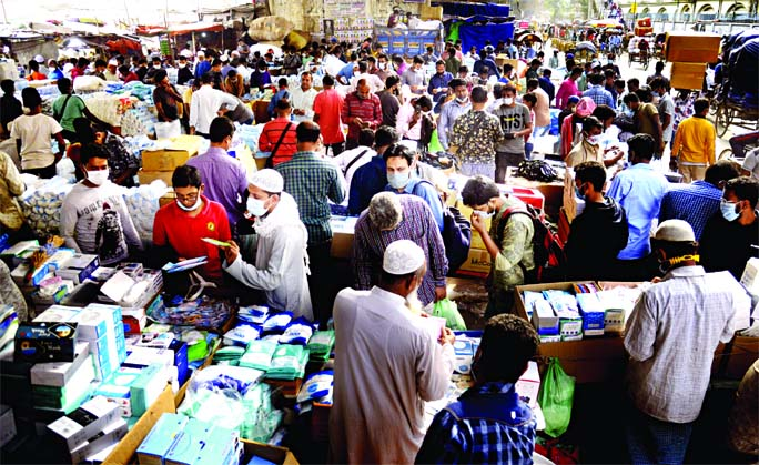 Traders are seen selling Covid-19 safety gears at a makeshift market under Babubazar Bridge in Old Dhaka with total disregard to social distancing norms on Wednesday amid the second wave of coronavirus pandemic striking the country.