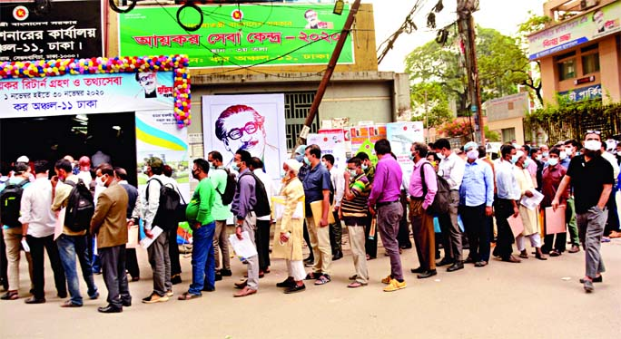 People form a long queue in front of Tax Commissioner's office (Tax Zone-11) to file their returns on Thursday with total disregard to physical distancing norm amid rising fatalities from Covid-19 in the country.