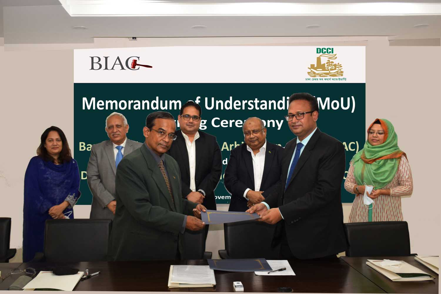 M A Akmall Hossain Azad, Director of Bangladesh International Arbitration Centre (BIAC) and Afsarul Arifeen, Acting Secretary General of DCCI, exchanging documents after signing a Memorandum of Understanding (MoU) at the BIAC secretariat in the city on Thursday. BIAC's CEO Muhammad A. (Rumee) Ali and DCCI President Shams Mahmud, among others, were present.
