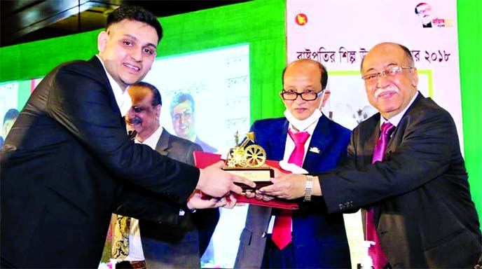 Ishmam Salam, Director of Envoy Group Limited, receiving the 'President's Industrial Development Award 2018' from Industries Minister Nurul Majid Mahmud Humayun MP at the Pan Pacific Sonargaon Hotel in the city on Monday.