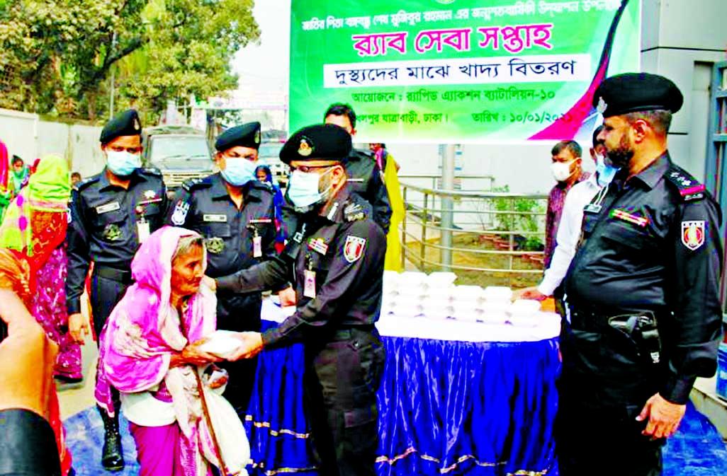 Members of RAB-10 distribute foods among destitute people marking the Homecoming Day of the Father of the Nation Bangabandhu Sheikh Mujibur Rahman at Dhalpur, Jatrabari in the capital on Sunday.