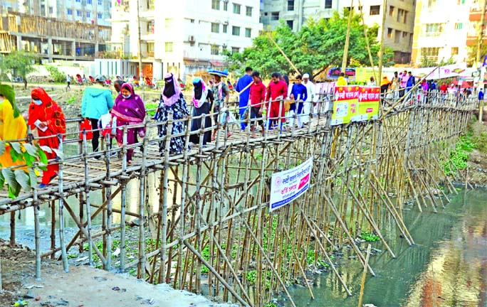 A bamboo bridge has been set up on the Rampura canal to connect the capital's Bonosree and Aftabnagar areas. Locals use the makeshift structure amid risk as their cry for building a concrete bridge has failed to bring any result. This photo was taken on Friday.