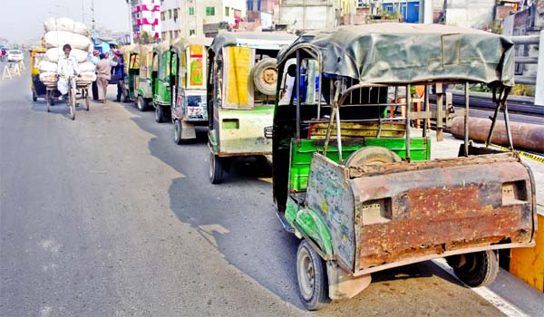 The two-stroke three-wheelers, known as baby-taxis, lined up on the Postogola Bridge in Dhaka to carry passengers. More than 100 two-stroke three-wheelers are still operating in Dhaka defying a ban imposed for their higher emissions. This photo was taken on Friday.
