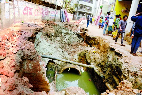Pedestrians walk beside a huge hole as construction firms excavate roads aimlessly as a result, the sufferings of the city dwellers mounted. This photo was taken from Boro Moghbazar area in the capital on Friday.