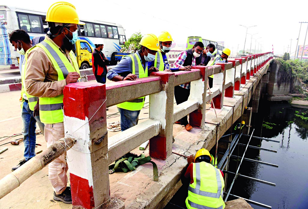 Engineers of Roads and Highways Department examine cracks on Salehpur Bridge near Aminbazar in Dhaka while carrying out repairing works of the bridge on Saturday.