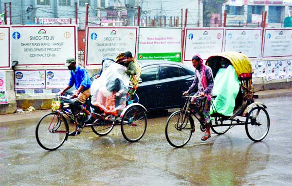 People use polythenes while riding rickshaws at Topkhana Road amid light rain in the capital on Wednesday.