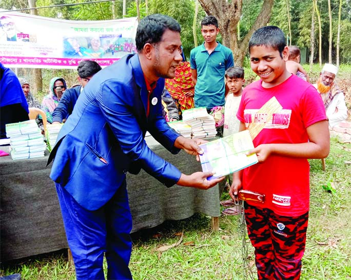 A child with special needs is receiving a new book at Khanmorich Disabled School in Bhangura Upazila of Pabna district on Wednesday.