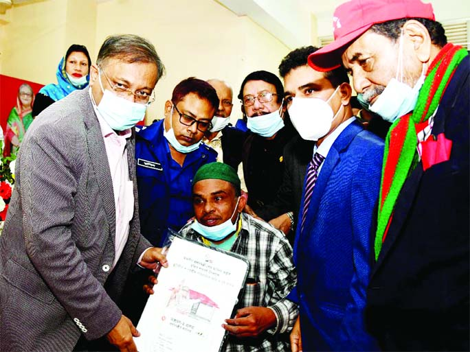 On behalf of Prime Minister Sheikh Hasina, Information Minister Dr Hasan Mahmud hands over deeds of houses and land among the landless families in Rangunia, Chattogram on Saturday marking 'Mujib Year'.