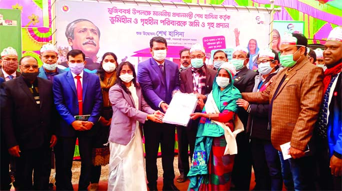 Rangpur DC Md Asib Ahsan hands over keys and documents of houses among the landless families in Gangachara Upazila in the district at a ceremony held on the upazila premises on Saturday. A total of 100 homeless families in the upazila got shelters as a gift from Prime Minister Sheikh Hasina on the occasion of the 'Mujib Barsho'.