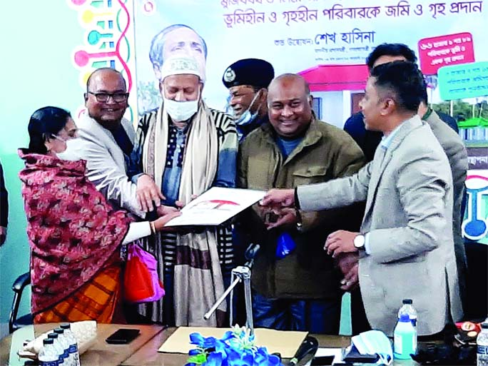 Syed Ashrafuzzaman, UNO of Bhangura (Pabna) hands over deed and documents of homes to ten landless and homeless families at the upazila conference room on Saturday marking the birth centenary of the Father of the Nation.