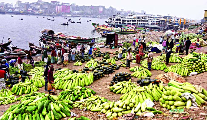 Wide varieties of vegetables come from the surrounding areas of Dhaka in the every early morning through the Buriganga River due to low transport cost. This photo taken on Saturday morning shows that traders pile up vegetables at the capital's Swarighat near the river bank.