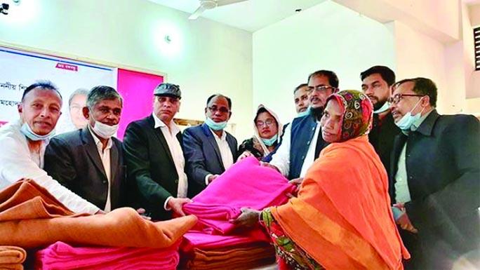 On behalf of the Education Minister  Dr Dipu Moni,  Chandpur Sadar  Upazila Chairman Nurul Islam Najim Dewan seen  handing over  5 hundred blankets among the cold hit people at  Sadar Upazila Auditorium on Wednesday.