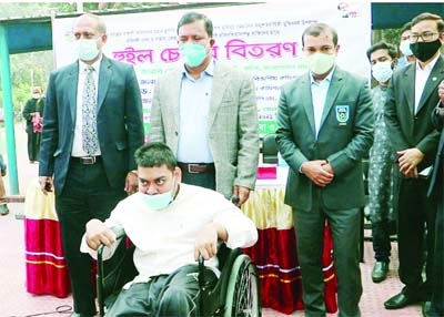 Md Sheikh Yousuf Harun, Secretary of the Ministry of Public Administration, distributes wheel-chairs at a programme held on the Naogaon DC office premises on Saturday.