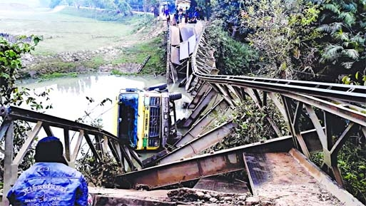 A bailey bridge collapses with a stone-laden truck in Dowarabazar upazila of Sunamganj on Saturday night.