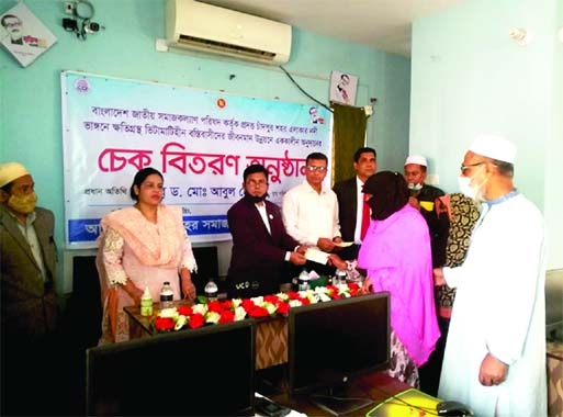 Social Welfare Ministry's  Joint Secretary Dr Md Abul Hossain handing over cheques  of Tk 4 thousand  (Total Tk one lakh) as govt grants  to each  of  a total of  25 poor slum  dwellers and river erosion victims in Chandpur  Sadar at a function at  Samaj Kalyan Office in Chandpur on Sunday. Samaj Kalyan Directorate, Chandpur's  Deputy Director Rajat Shuvro Sarker  was also present.