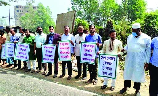 Brickfield owners form a human chain on Chattogram-Cox's Bazar Highway in Lohagara on Tuesday seeking Prime Minister's intervention to keep up their brick manufacturing activities.